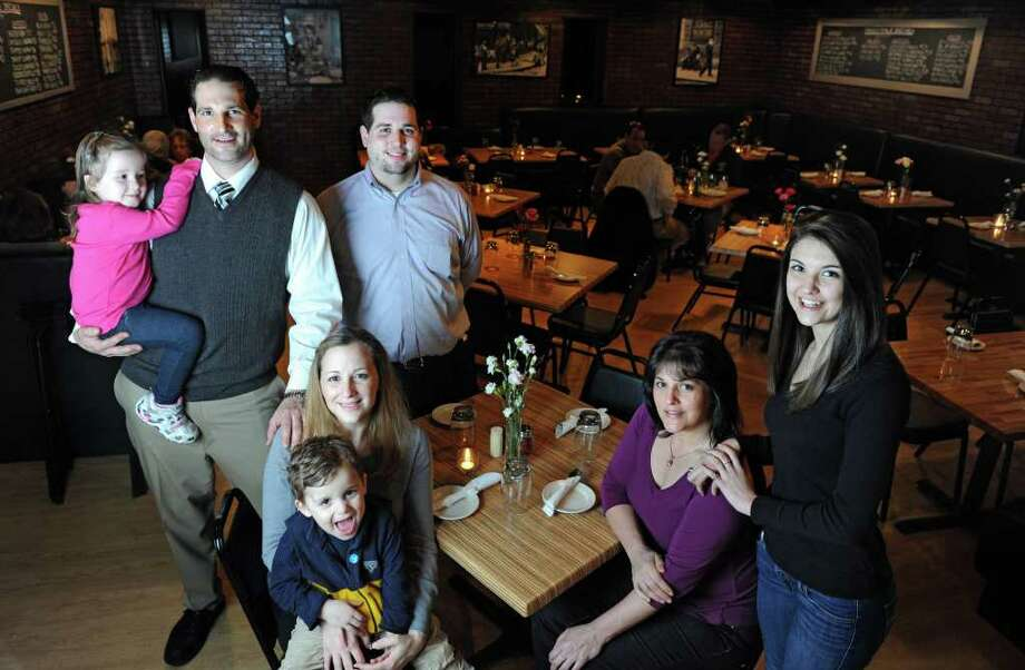 Owners Mathew and Kelly Calandro, left, with Ali, 4, and Bobby, 3, pose in their new restaurant, Verace, with manager Lou Como, center, and family members and employees Debbie Palko and Becca Palko, 16. Photo: Autumn Driscoll / Connecticut Post