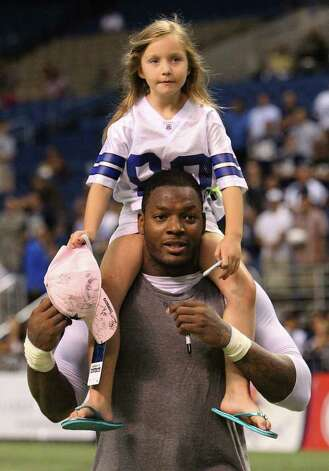 Maya Friedman, 6, of Sugarland rides on the shoulders of Cowboys tight end Martellus Bennett as they went around the field gathering autographs at the end of the afternoon session of the Dallas Cowboys training camp at the Alamodome on Wednesday, Aug. 3, 2011. Kin Man Hui/kmhui@express-news.net Photo: KIN MAN HUI, SAN ANTONIO EXPRESS-NEWS / SAN ANTONIO EXPRESS-NEWS