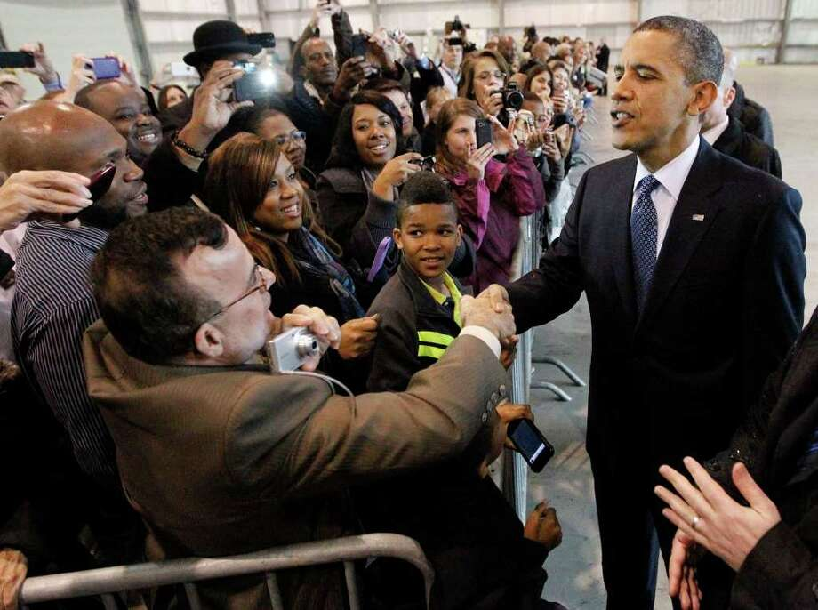 President Barack Obama greets supporters inside a hanger during his arrival at Ellington Airport, Friday, March, 9, 2012, in Houston. Photo: AP