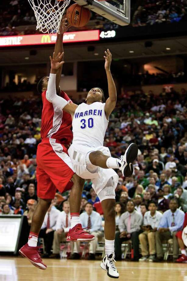 Fort Bend Travis's Andrew Harrison blocks a shot under the basket by Warren's Jerell Ellis during the second quarter of their 5A state semifinal game at the Frank Erwin Center in Austin on March 9, 2012.  Fort Bend Travis won the game 85-72.  MARVIN PFEIFFER/ mpfeiffer@express-news.net Photo: MARVIN PFEIFFER, Marvin Pfeiffer/ Express-News / Express-News 2012