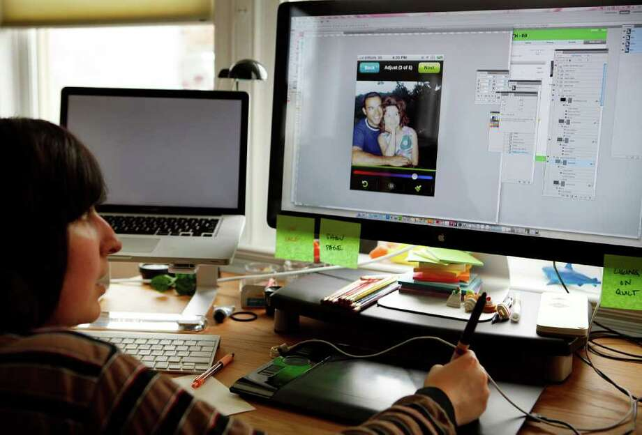 Designer Liz Gershman and 1000memories art director works on designing how photo image adjusting tools will appear on the 1000memories app (shown on the computer screen) in their office in San Francisco, California, February 29, 2012. Photo: LiPo Ching, MCT / San Jose Mercury News