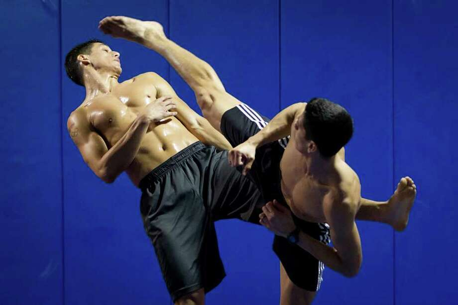 Mark Lopez sends a kick at the head of brother Steven during a training session at the Lopez Taekwondo Academy in preparation for the Olympic trials. Photo: Smiley N. Pool / © 2012  Houston Chronicle