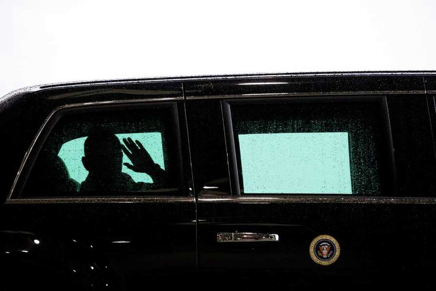 President Barack Obama waves from the presidential motorcade, shortly after arriving on Air Force On
