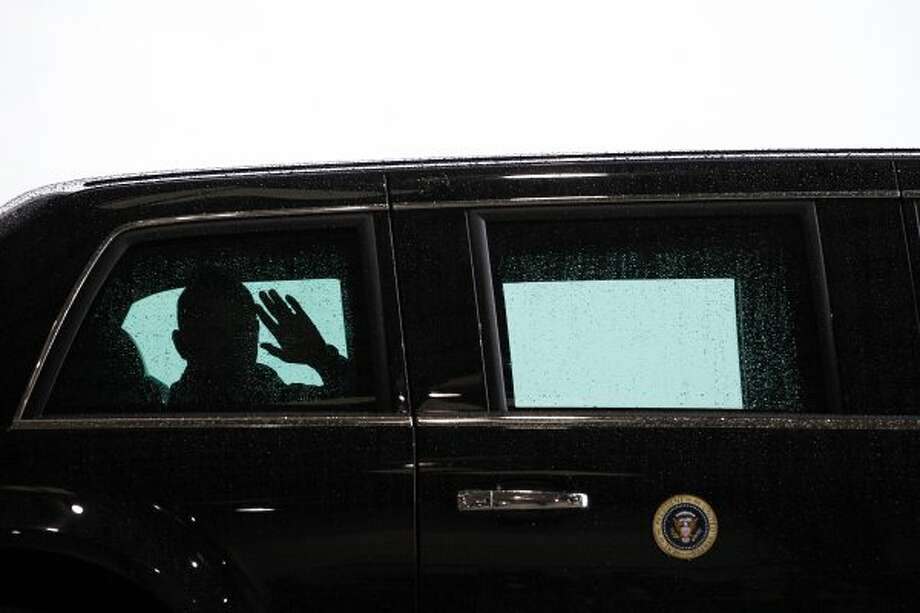 He waves at Houstonians watching the presidential motorcade at Ellington. (Todd Spoth / For The Chronicle)