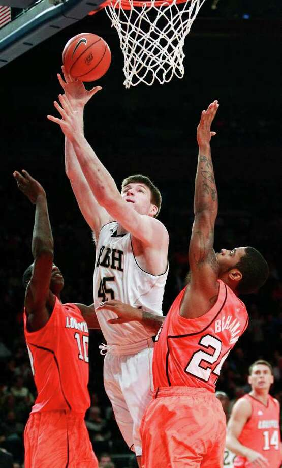 Notre Dame's Jack Cooley (45) drives past Louisville's Gorgui Dieng (10) and Chane Behanan (24) during the first half of an NCAA college basketball game in the semifinals of the Big East Conference tournament in New York, Friday, March 9, 2012. Photo: Frank Franklin II