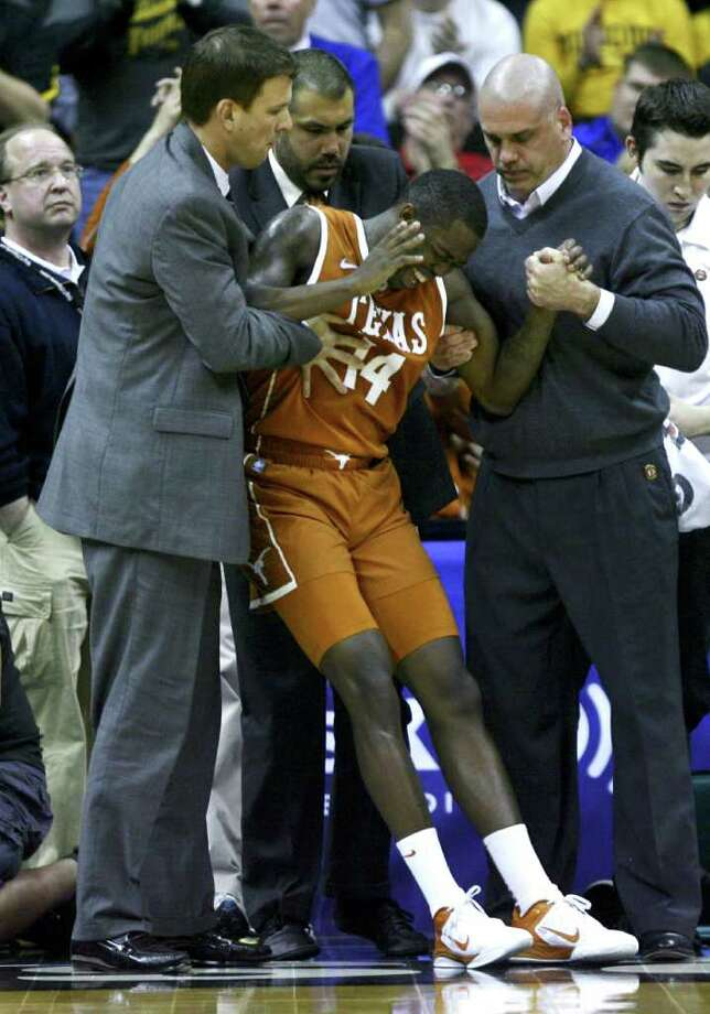 KANSAS CITY, MO - MARCH 09:  J'Covan Brown #14 of the Texas Longhorns is helped to his feet after being injured while playing against the Missouri Tigers in the second half during the semifinals of the Big 12 Basketball Tournament March 09, 2012 at Sprint Center in Kansas City, Missouri. Photo: Ed Zurga, Getty Images / 2012 Getty Images