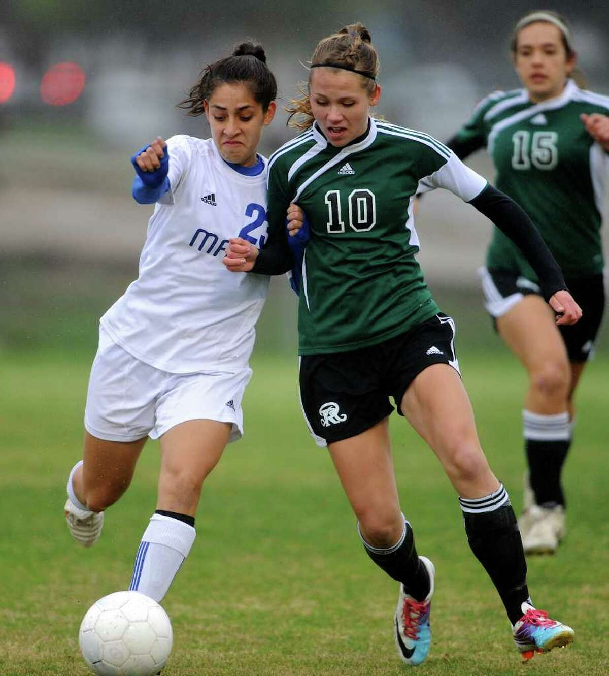 MacArthur senior Stephanie Figueroa (23) battles for control of the ball with Reagan senior Monica Penfield (10) during a 26-5A Girls Varsity Soccer Match between the Reagan Rattlers and the MacArthur Brahmas at the Blossom Soccer Stadium East Field In San Antonio, Texas on March 9, 2012. John Albright / Special to the Express-News.
