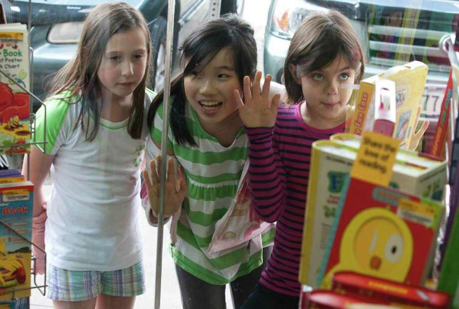 Nine-year-olds Camille McFarland, Mizuki Kai, and Anne Johnson peek into the Half Price Books in the Rice Village. They also like to buy ice cream in the shopping area, which has about 360 businesses. Photo: J. Patric Schneider / Houston Chronicle