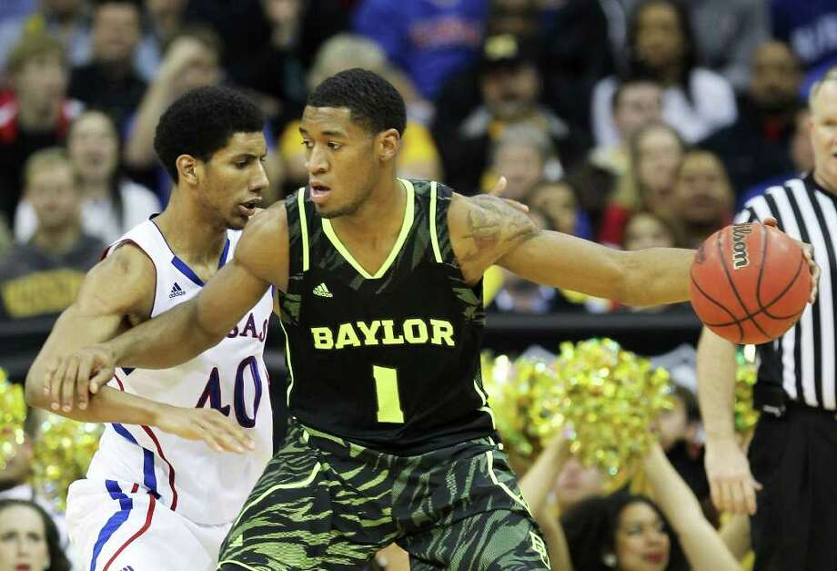 Perry Jones III, right, creates room to maneuver against Kansas' Kevin Young during Friday's Big 12 semifinal game. Jones led Baylor with 18 points. Photo: Jamie Squire / 2012 Getty Images