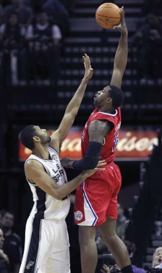The Clippers' DeAndre Jordan skies over Tim Duncan with a hook shot.
