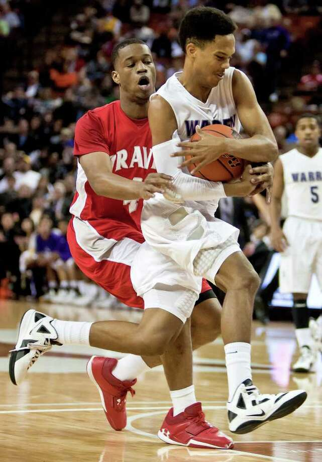 Warren's Jerrell Ellis tries to protect the ball from Fort Bend Travis's Christian Crocket as he makes his way to the basket during the first quarter of their 5A state semifinal game at the Frank Erwin Center in Austin on March 9, 2012.  Travis won the game 85-72.  MARVIN PFEIFFER/ mpfeiffer@express-news.net Photo: MARVIN PFEIFFER, Express-News / Express-News 2012