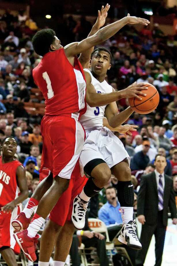 Warren's Marcus Keene (right) tries to get a shot off under the basket past Fort Bend Travis's John Burnett during the fourth quarter of their 5A state semifinal game at the Frank Erwin Center in Austin on March 9, 2012.  Fort Bend Travis won the game 85-72.  MARVIN PFEIFFER/ mpfeiffer@express-news.net Photo: MARVIN PFEIFFER, Express-News / Express-News 2012