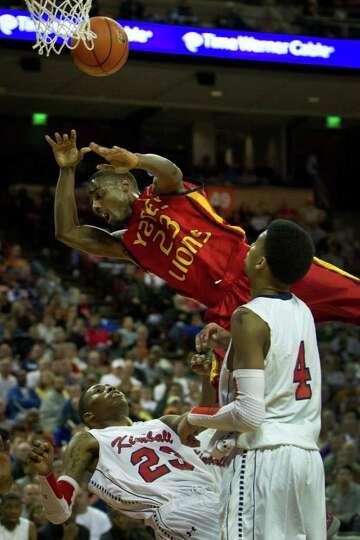 Houston Yates guard Darrion Martin flies over Dallas Kimball's D'Angelo Allen