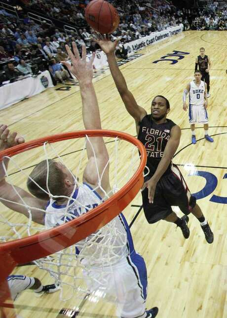 Florida State's Michael Snaer (right), floating a shot over Duke's Miles Plumlee, had 16 points to lift Florida State to its second ACC tournament title game. Photo: AP