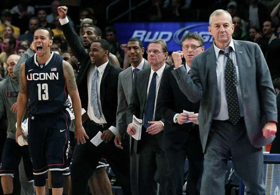 Shabazz Napier, on the left, and Jim Calhoun, on the right, bracket UConn's coaching staff and celebrate the Huskies' Big East tournament victory over West Virginia on Wednesday. Photo: Jim McIsaac/Getty Images / 2012 Getty Images