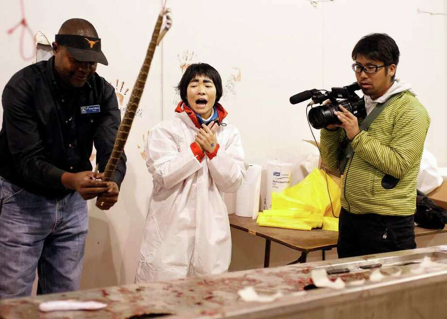 "Ayako Imoto reacts as Sweetwater Jaycee Danny Williams guts a rattlesnake during the 54th annual Rattlesnake Roundup at Nolan County Coliseum in Sweetwater, Texas on Friday, March 9, 2012. According to Imoto's translator, Jonathan Hinton, Imoto is, ""a Japanese TV host known for traveling the world [and] interacting with wild animals."" The event is the largest in the world and is held every year in the second weekend of March. Photo: Michael Miller, San Antonio Express-News / © 2012 San Antonio Express-News"
