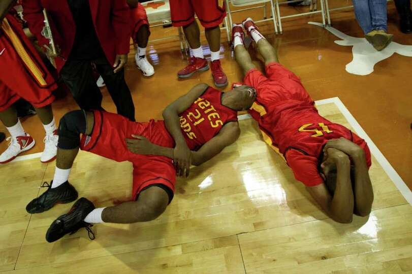 Houston Yates guard Damyean Dotson (21) and center Maurice Ellis (15) collapse to the court after a