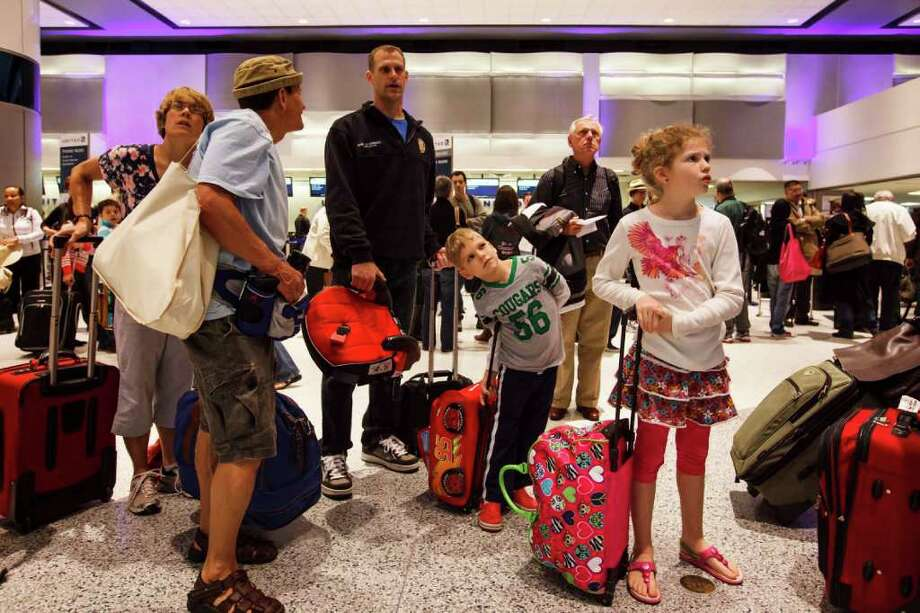 Mark Van Berschot III, 6, center, and his sister Emma, 8, look at the departure schedule along with their father Mark as they wait in line Saturday at Bush Intercontinental Airport to fly on United Airlines. Photo: Michael Paulsen / © 2012 Houston Chronicle