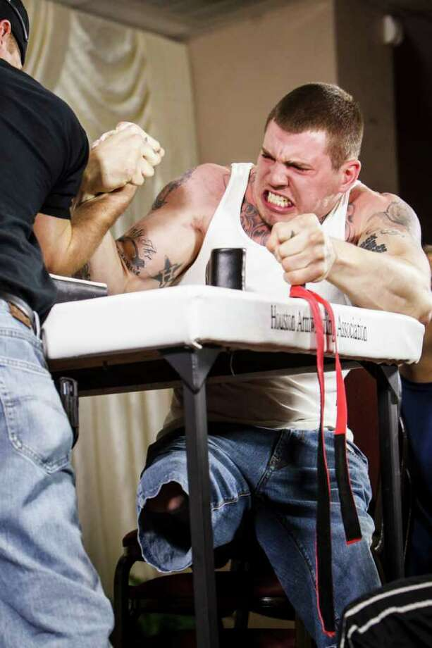 Zack Ruhl took top prize in his weight division during Saturday's arm wrestling tournament. Photo: Michael Paulsen / © 2012 Houston Chronicle