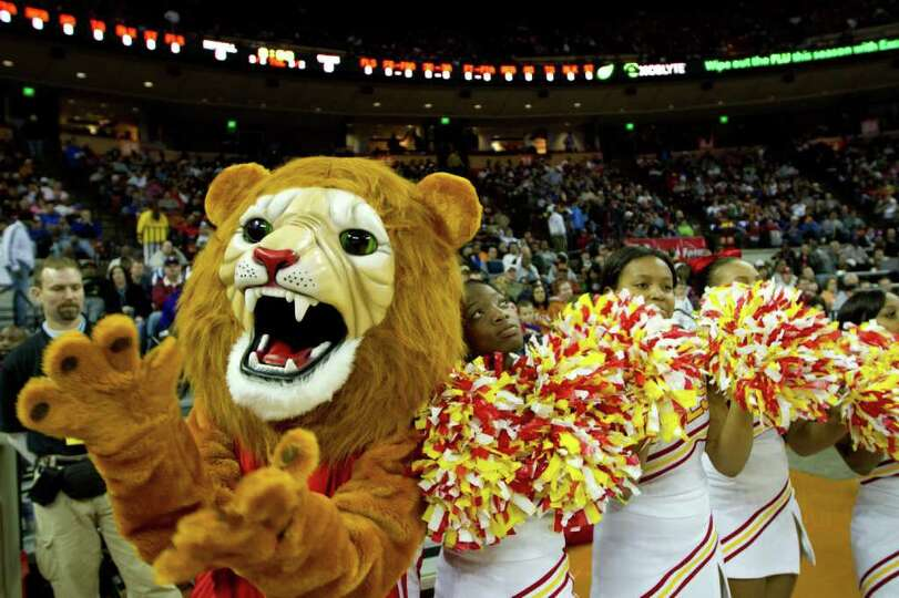 The Houston Yates Lions mascot and cheerleaders applaud their team as they take the court to face Da