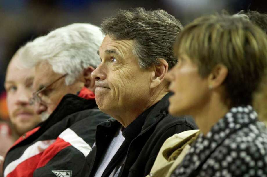 Texas Gov. Rick Perry watches Houston Yates face Dallas Kimball during the first half of the UIL class 4A state championship high school basketball game at the Erwin Center on Saturday, March 10, 2012, in Austin.  Smiley N. Pool / Houston Chronicle ) Photo: Smiley N. Pool, Houston Chronicle / © 2012  Houston Chronicle
