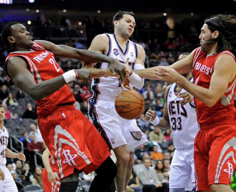 New Jersey Nets' Jordan Farmar loses the ball as it is stripped by Houston Rockets' Samuel Dalembert, left, of Haiti, and Luis Scola, right, of Argentina, during the first quarter of an NBA basketball game Saturday, March 10, 2012, in Newark, N.J. (AP Photo/Bill Kostroun) Photo: Bill Kostroun, Associated Press / FR51951 AP