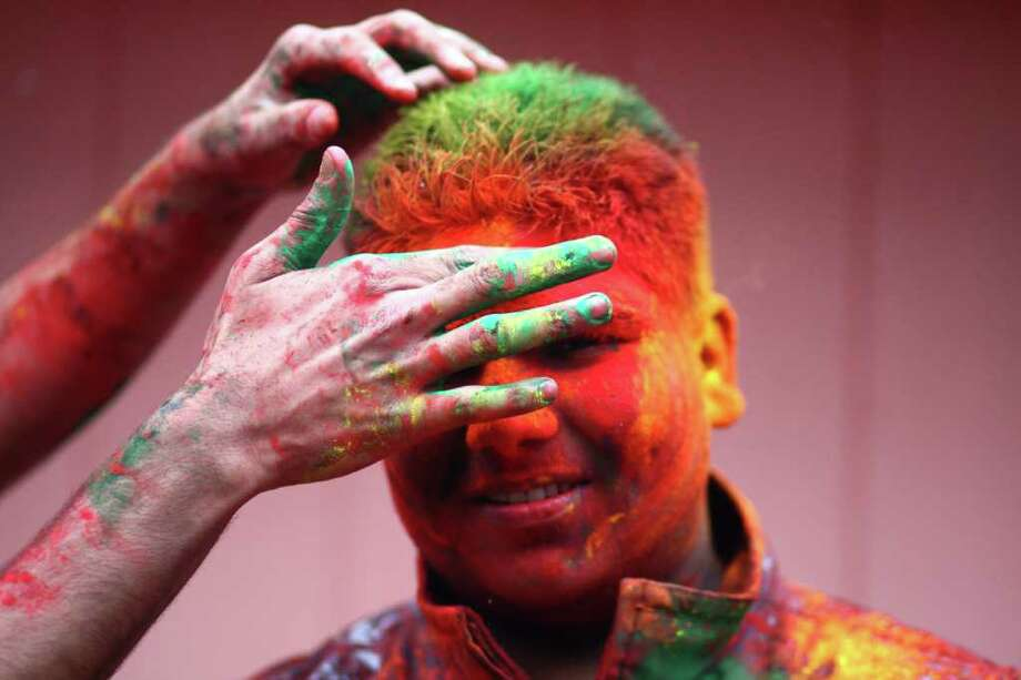 People participate in a Holi festival at the Sanatan Dharma Hindu Temple and Cultural Center in Maple Valley on Saturday, March 10, 2012. Holi, the Festival of Colors, is a Hindu festival welcoming spring. It is most well-known for the vibrant bursts of gulal, the powedered dye, that festivalgoers throw on each other. Photo: JOSHUA TRUJILLO / SEATTLEPI.COM