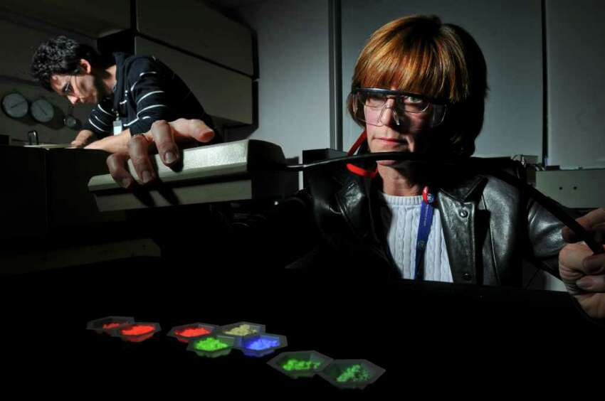 Senior chemist Holly Comanzo uses an ultraviolet light to show the variations in shade of phosphor powder in a Phosphor Lab at the GE Global Research Center on Thursday March 8, 2012 in Niskayuna, N.Y. Researchers there are trying to find a replacement for rare earth materials used in phosphors for lighting. Working with her in the lab is scientist Floren Garcia. (Philip Kamrass / Times Union )