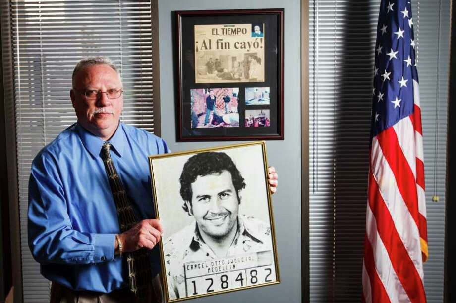 The DEA's new Houston Division Chief, Javier Pena, holds a photo of the first booking mug shot of Pablo Escobar that he got while working on the case years earlier, while at his office, Tuesday, Feb. 28, 2012, in Houston.    On the wall behind Pena is a collection of photographs and original newspaper clipping of Escobar, one of the world's most famous drug traffickers. Photo: Michael Paulsen, Houston Chronicle / © 2012 Houston Chronicle