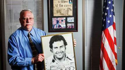The DEA's new Houston Division Chief, Javier Pena, holds a photo of the first booking mug shot of Pablo Escobar that he got while working on the case years earlier, while at his office, Tuesday, Feb. 28, 2012, in Houston.    On the wall behind Pena is a collection of photographs and original newspaper clipping of Escobar, one of the world's most famous drug traffickers.