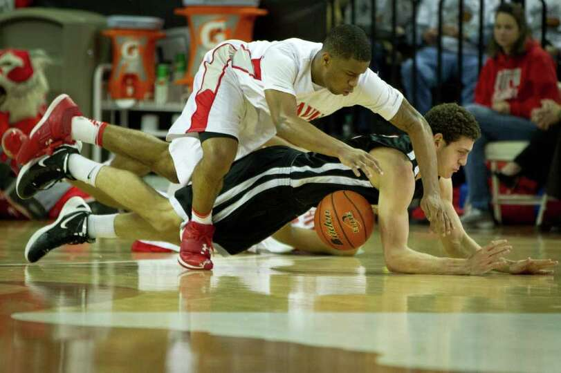 Fort Bend Travis forward Christian Crockett (4) dives for a loose ball against Lewisville Marcus cen