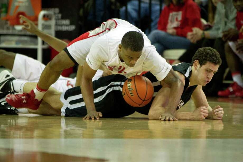 Fort Bend Travis forward Christian Crockett (4) dives for a loose ball against Lewisville Marcus center Jared Hamilton (31) during the first half of the UIL class 5A state championship high school basketball game at the Erwin Center on Saturday, March 10, 2012, in Austin. Photo: Smiley N. Pool, Houston Chronicle / © 2012  Houston Chronicle