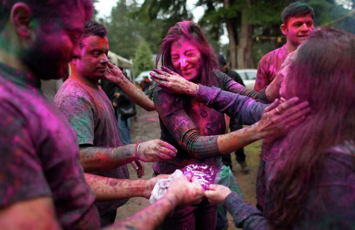 Participants rub powdered color on each other during a Holi festival at the Sanatan Dharma Hindu Temple and Cultural Center in Maple Valley on Saturday, March 10, 2012. Holi, the Festival of Colors, is a Hindu festival welcoming spring. It is most well-known for the vibrant bursts of gulal, the powdered dye, that festivalgoers throw on each other.