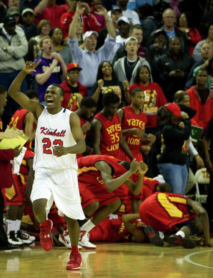 Dallas Kimball forward Sheldon Yearwood (22) celebrates the win as Yates players collapse to the court at the final buzzer of the Class 4A state championship game in Austin. Photo: Smiley N. Pool / © 2012  Houston Chronicle