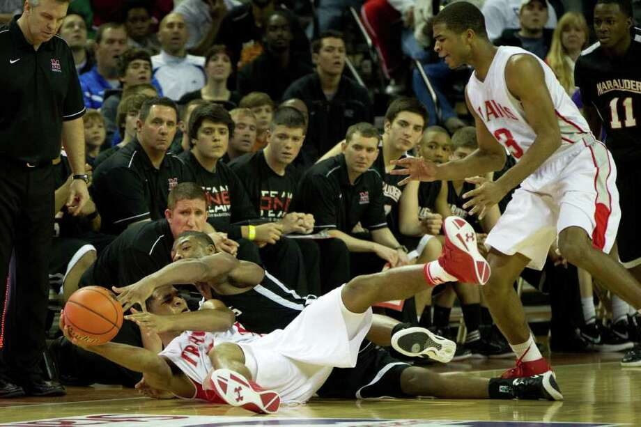 Fort Bend Travis guard Andrew Harrison is smothered by Lewisville Marcus guard Marcus Smart as he hits the floor for a loose ball and tries to get off a pass to his twin brother Aaron Harrison (3) during the second half of the UIL class 5A state championship high school basketball game at the Erwin Center on Saturday, March 10, 2012, in Austin.  Lewisville Marcus won the game 56-52. Photo: Smiley N. Pool, Houston Chronicle / © 2012  Houston Chronicle