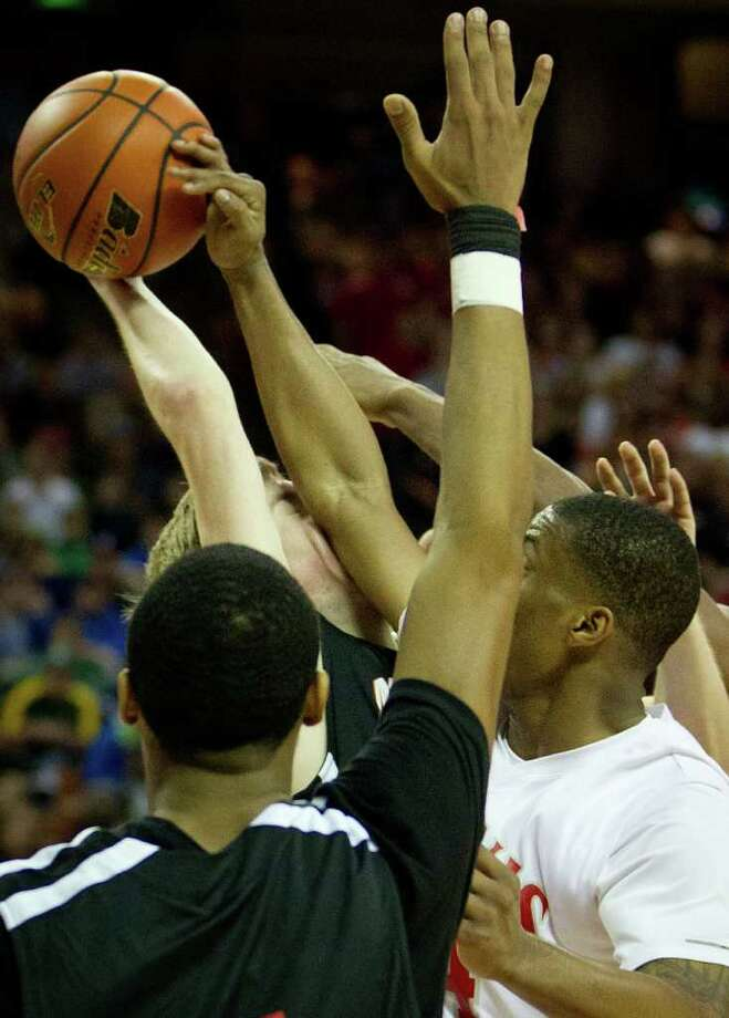Lewisville Marcus forward Matt Ledford gets an arm in the face from Fort Bend Travis forward Christian Crockett during the second half of the UIL class 5A state championship high school basketball game at the Erwin Center on Saturday, March 10, 2012, in Austin.  Lewisville Marcus won the game 56-52. Photo: Smiley N. Pool, Houston Chronicle / © 2012  Houston Chronicle