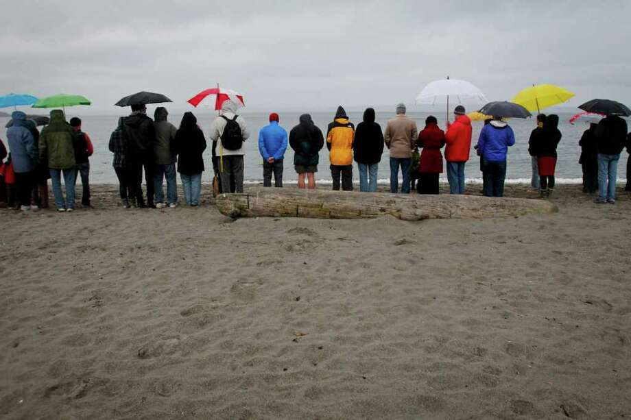 People gather for a memorial remembering the victims of the 2011 tsunami and nuclear disaster in Japan at Golden Gardens Park Beach in Seattle on Saturday, March 10, 2012. The vigil, which was organized by Artists for Japan, by included singing, silent prayer, and a drum performance by the Seattle Kokon Taiko group. Photo: JOE DYER / SEATTLEPI.COM