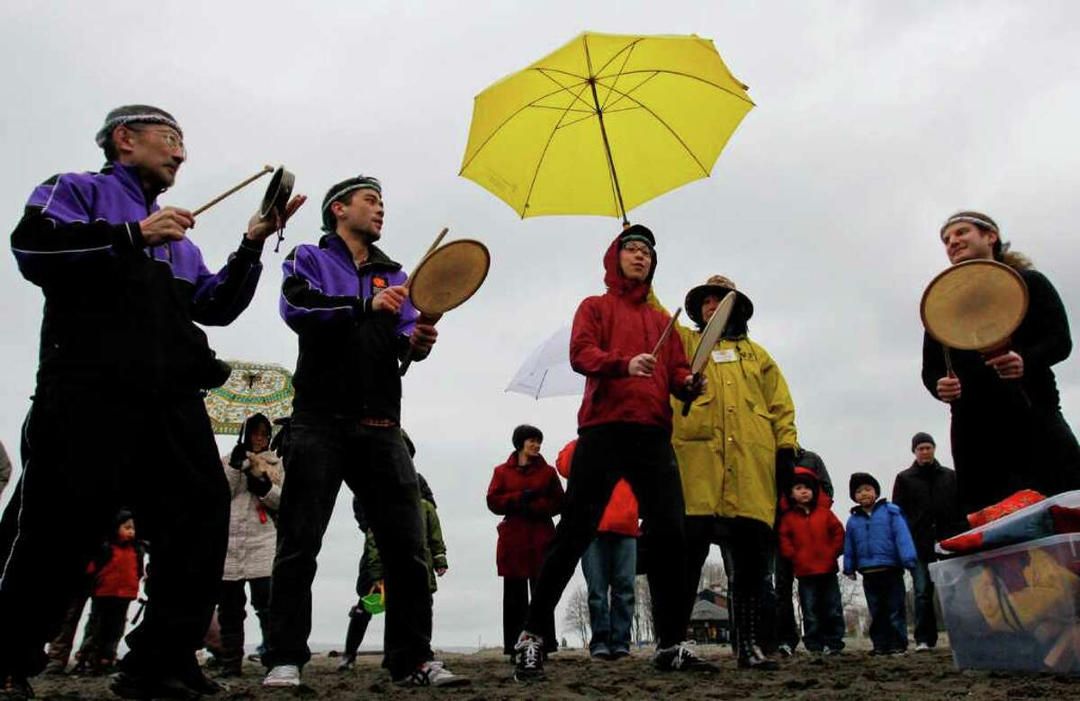 People gather for a memorial remembering the victims of the 2011 tsunami and nuclear disaster in Japan at Golden Gardens Park Beach in Seattle on Saturday, March 10, 2012. The vigil, which was organized by Artists for Japan, by included singing, silent prayer, and a drum performance by the Seattle Kokon Taiko group.