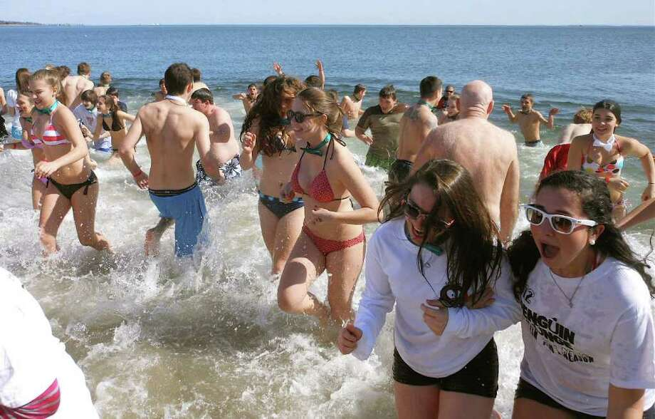 It was a quick dip for a good cause Saturday at Compo Beach as about 450 people joined the Penguin Plunge to benefit the Special Olympics of Connecticut. Photo: Mike Lauterborn / Westport News contributed