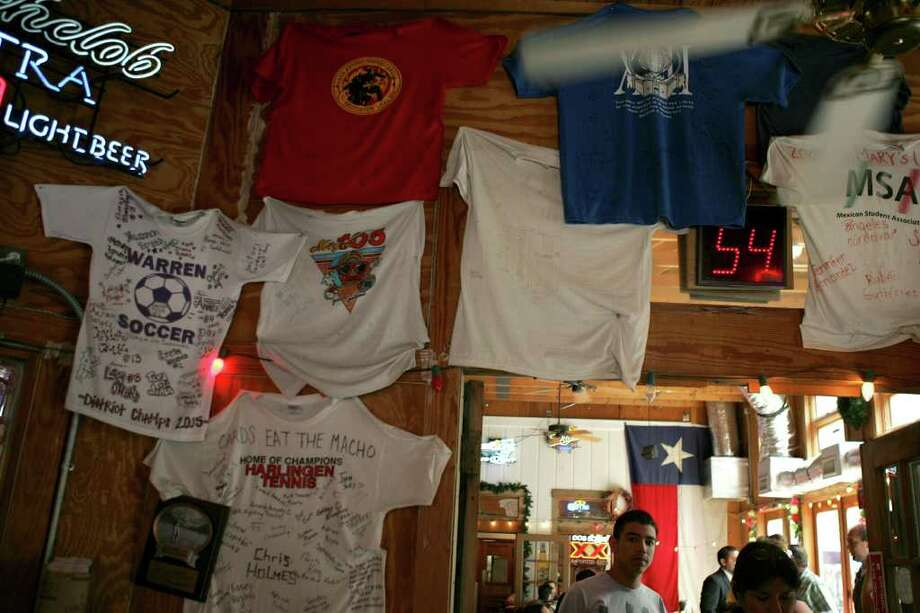 The walls of Chris Madrid's are covered in t-shirts given to him over the years from customers. Photo: KEVIN GEIL, SAN ANTONIO EXPRESS-NEWS / SAN ANTONIO EXPRESS-NEWS