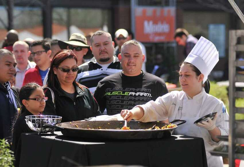 Julianna Glassaos cooks paella for a long line of waiting people during the Corona Paella Challenge at the Pearl Brewery Sunday.