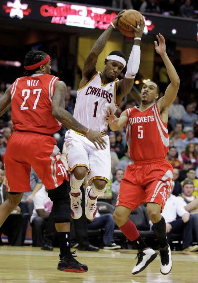 Cleveland Cavaliers' Daniel Gibson (1) jumps between Houston Rockets center Jordan Hill (27) and Courtney Lee (5) in the first quarter in an NBA basketball game Sunday, March 11, 2012, in Cleveland. (AP Photo/Tony Dejak) Photo: Tony Dejak, Associated Press / AP 2010