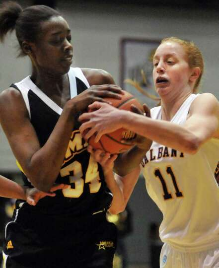 UAlbany's #11 Julie Forster, at right, and UMBC 's #34 Tope Obajolu struggle over a rebound in the c