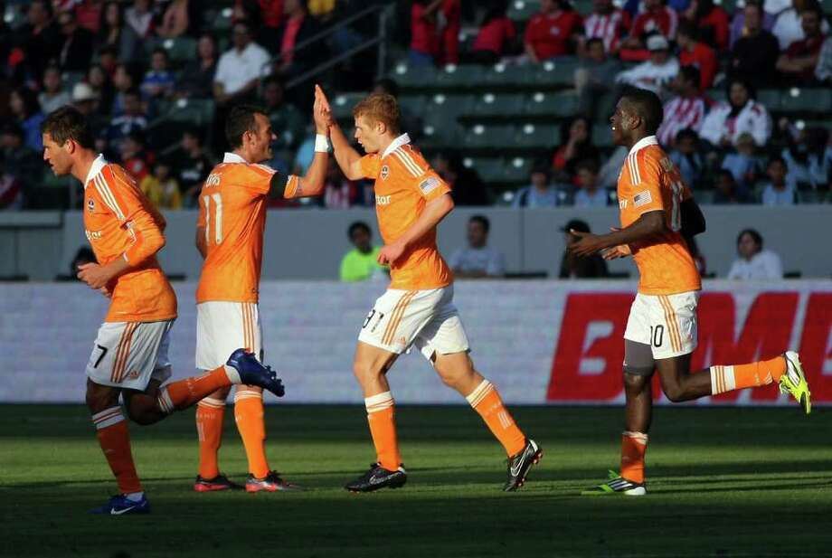 CARSON, CA - MARCH 11:  Andre Hainault #31 of the Houston Dynamo celebrates his second half goal with teammate Brad Davis #11 after scoring in the 90th minute against Chivas USA during their MLS match at The Home Depot Center on March 11, 2012 in Carson, California. Photo: Victor Decolongon, Getty Images / 2012 Getty Images