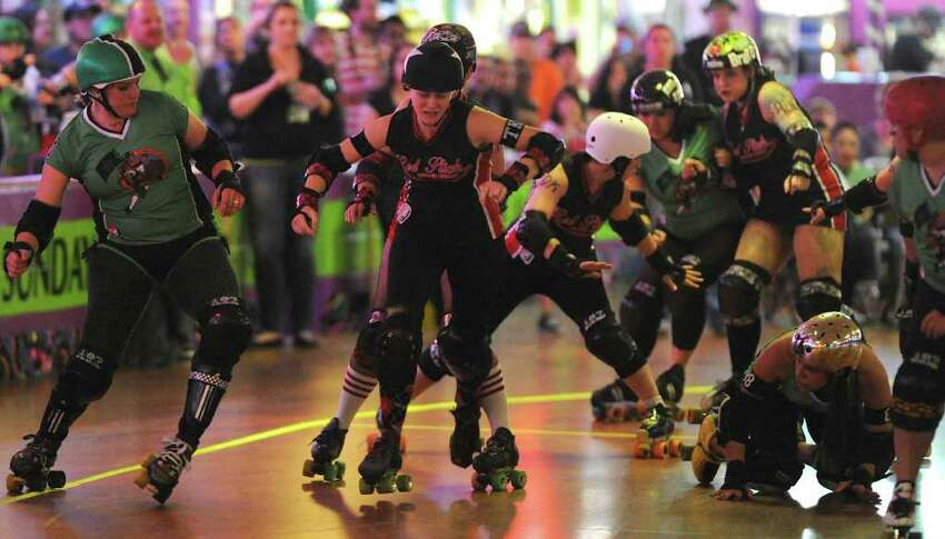 Members of the Las Tejanas and Red Stick Roller Derby teams compete against each other during the Alamo City Roller Girls season opener at the Rollercade In San Antonio, Texas on March 11, 2012.