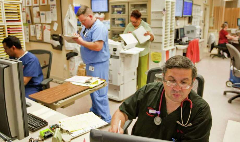 Dr. Tarek Koussayer, right, goes over his patient notes Thursday at Mainland Medical Center's emergency room in Texas City. Koussayer says patients turned away by UTMB often land in the Mainland ER. Photo: Nick De La Torre / © 2012  Houston Chronicle