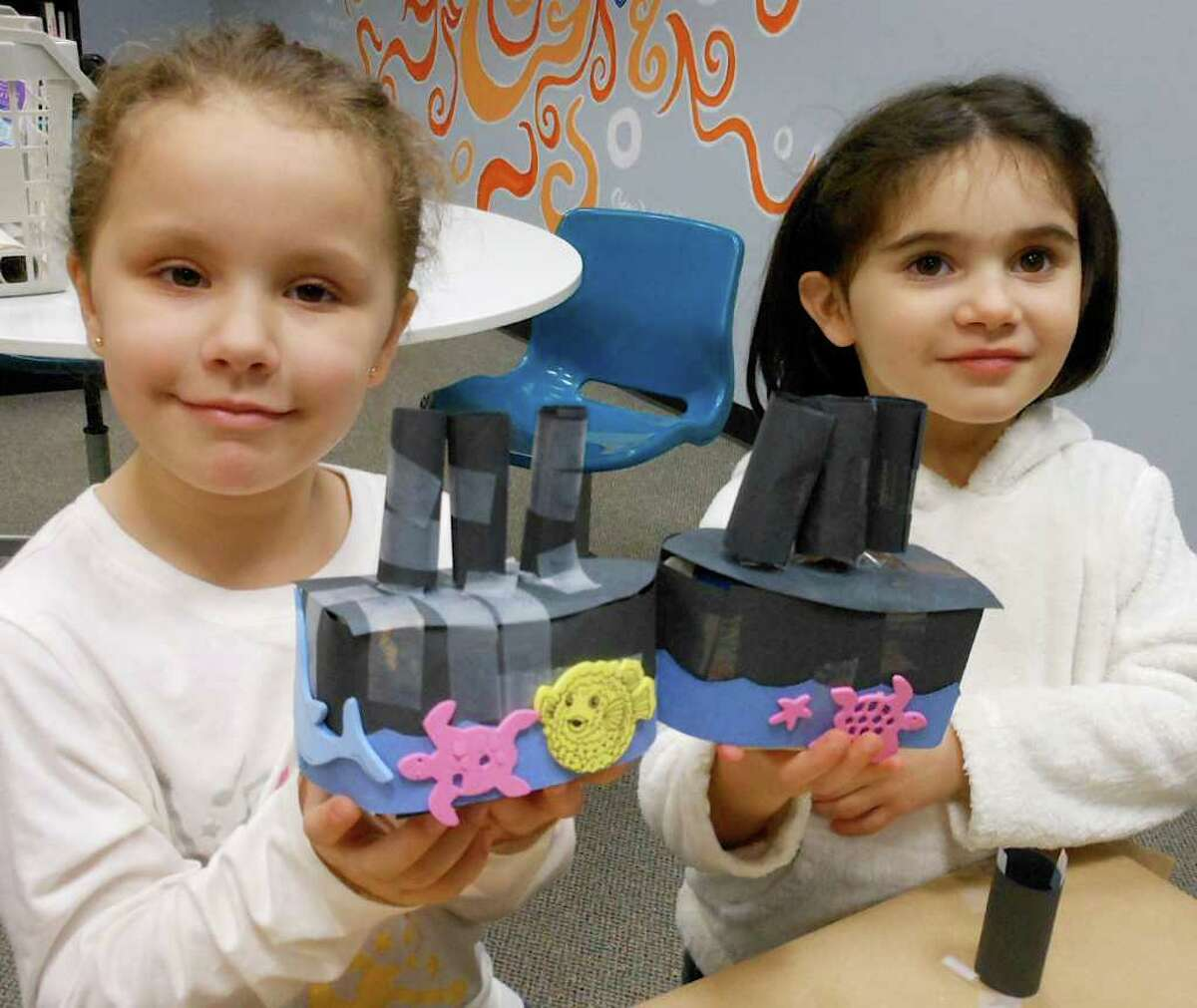"""Five-year-olds Virginia Caceres and Luca DeMassa show off Titanic replicas they made Friday during a """"One Book, One Town"""" program at the Fairfield Woods Branch Library."""