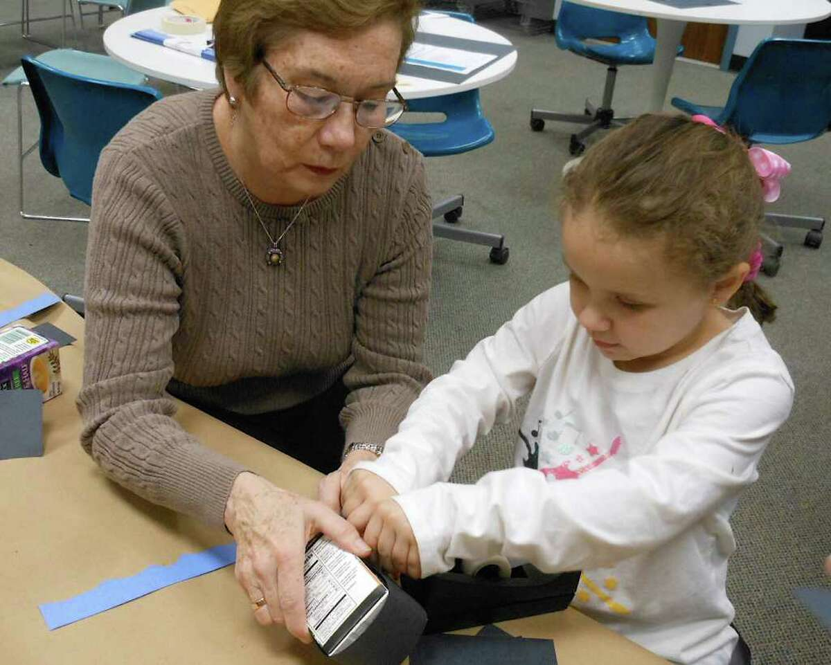 Five-year-old Virginia Caceres works with her grandmother Amparo Orban to create a mini Titanic replica at the Fairfield Woods Branch Library on Friday.