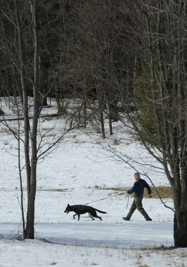 "Trooper Matthew Carniglia takes his partner ""Dale"" out for tracking practice during K-9 training at the New York State Police K-9 Training facility in Cooperstown, N.Y. March 7, 2012.  ( Skip Dickstein / Times Union) Photo: Skip Dickstein / 2011"