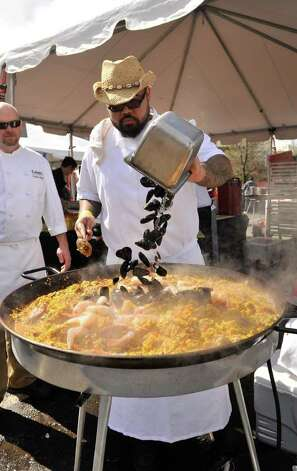 Chef Gabriel Ibarra adds mussels to his paella as Parker Koch looks on during the Corona Paella Challenge at the Pearl Brewery Sunday. Photo: Robin Jerstad, Robin Jerstad/For The Express-News